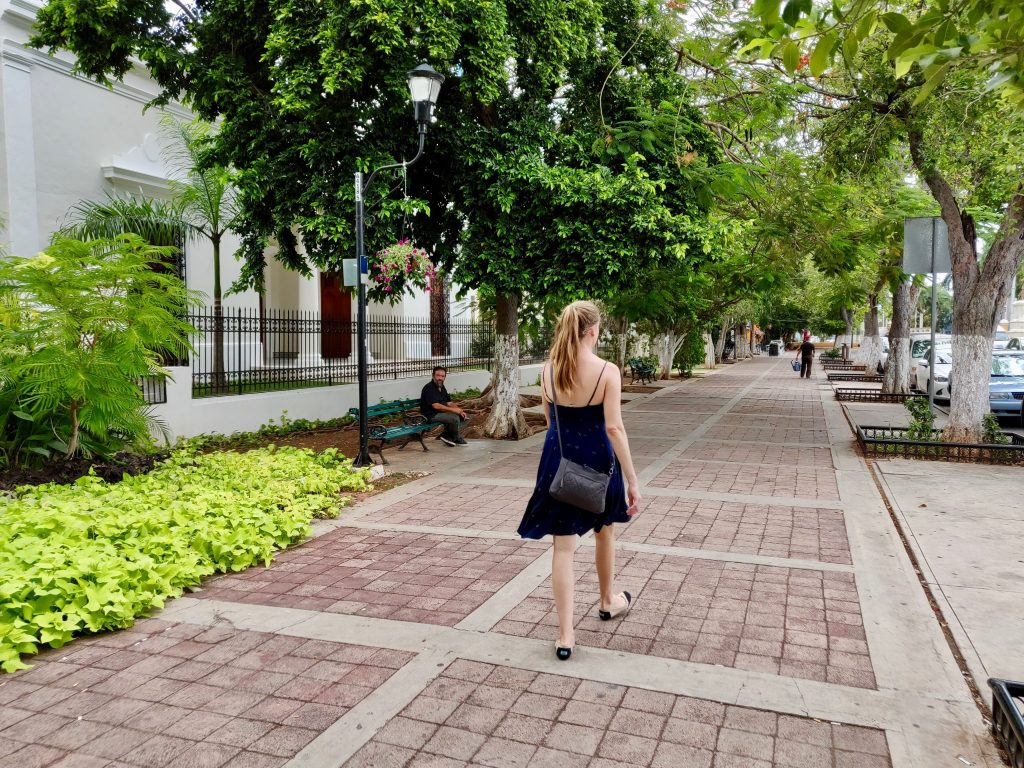 woman walking on sidewalk on Paseo de Montejo Merida
