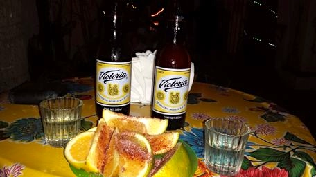Mezcal shots with sour orange slices, sal de gusano, and a beer back.