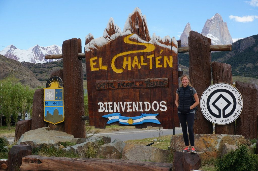 Heather standing in front of El Chalten sign with Fitz Roy mountains
