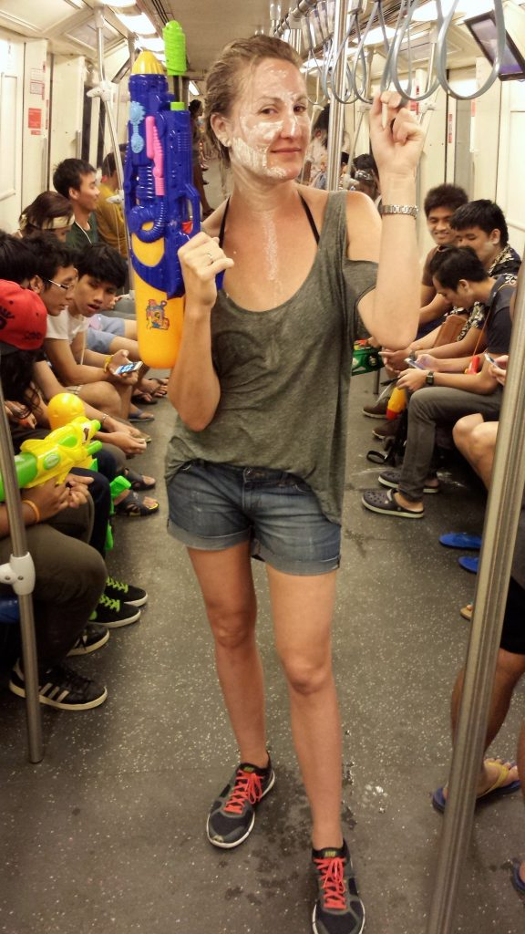 A soaking wet Heather poses with a water gun on the subway in Bangkok