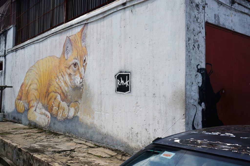 Penang street art with big rat hiding from a big orange cat