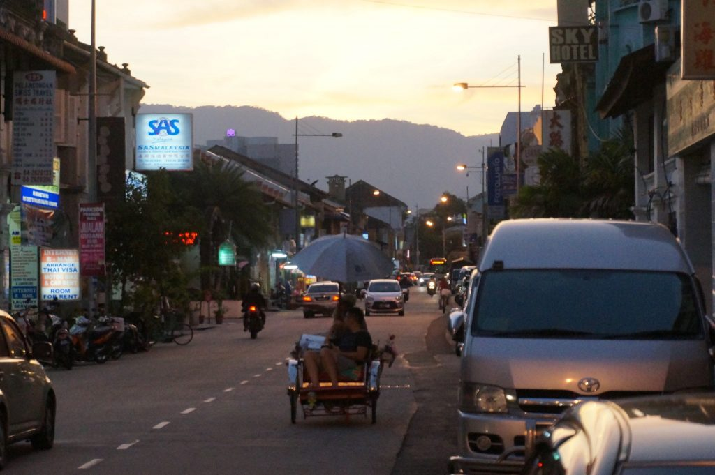 Trishaw - three wheeled bicycle taxi - on Penang street at sunset