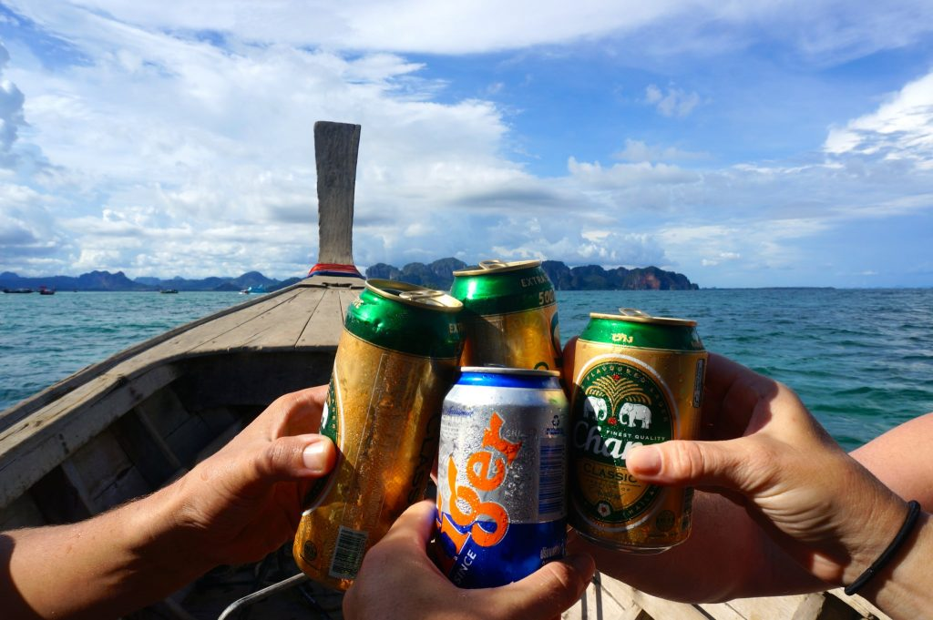 cheersing Thai beers on longtail boat during 4-island tour from Railay