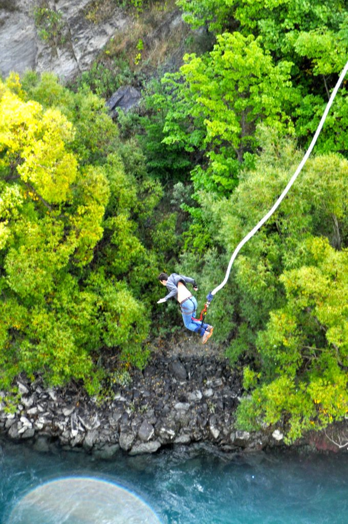 Man (John) in air bungee jumping off the Kawarau Bridge into the Kawarau River Gorge below