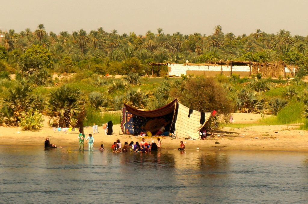 children playing on the shore of the Nile River