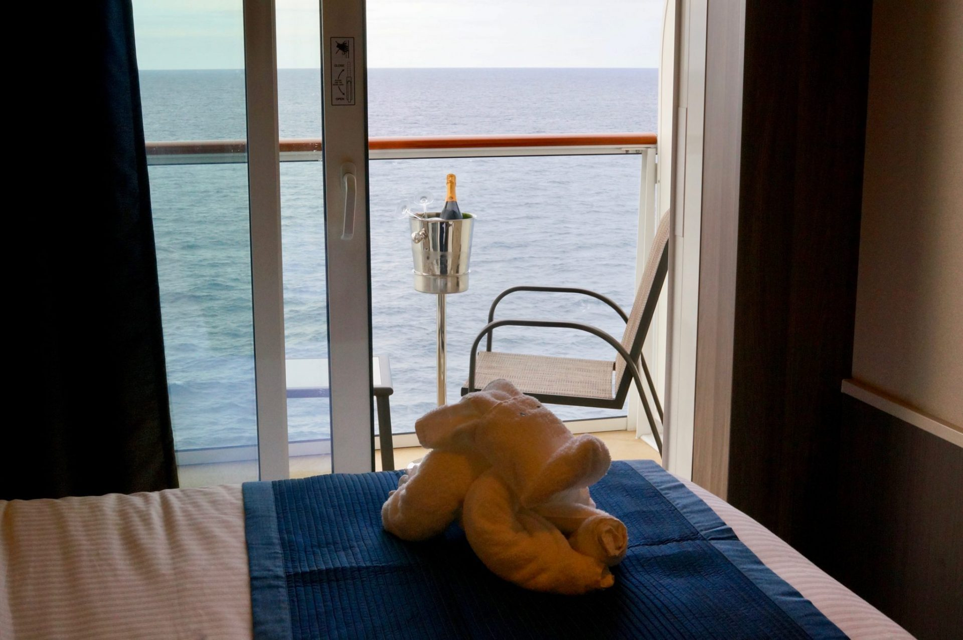 Towel animal on bed of free balcony upgrade cabin on Norwegian Bliss