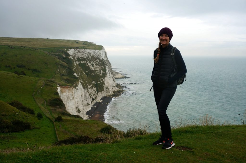 Heather standing at the edge of the white cliffs of dover england on a cloudy overcast morning before our cruise