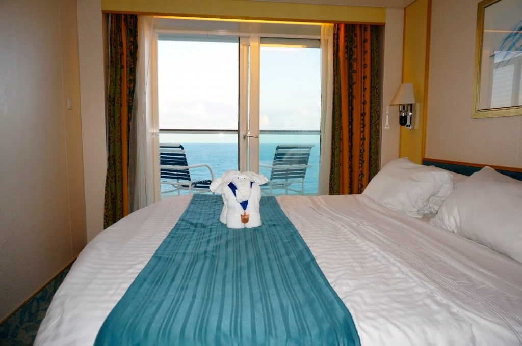 A towel animal sits on the bed that we show how to get a free balcony upgrade on a cruise ship