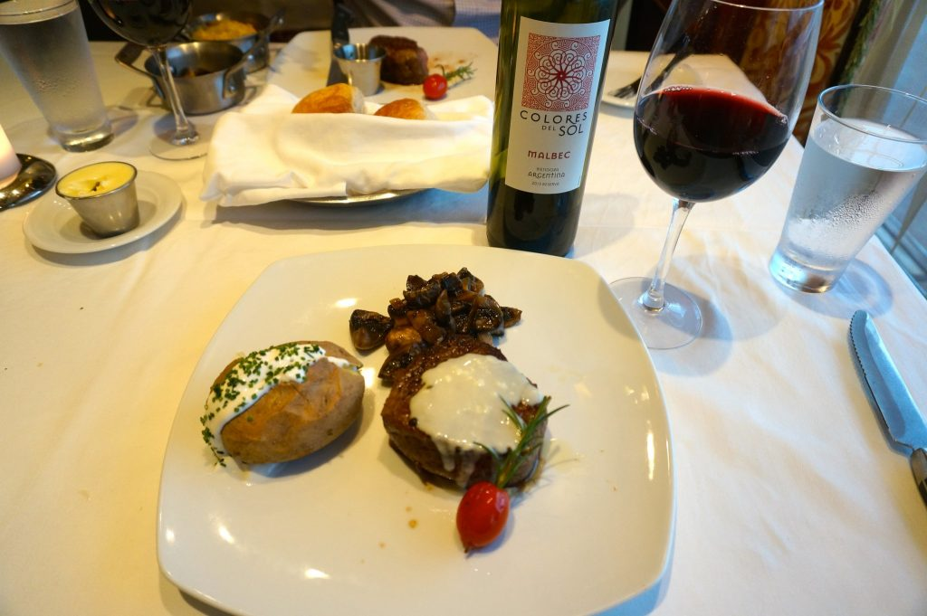 Filet Mignon steak with baked potato and Malbac wine at Cagney's Steakhouse restaurant on the Norwegian Star Cruise ship