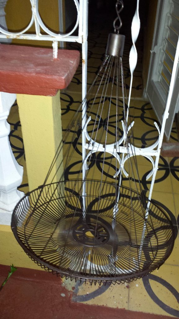 a chandelier light fixture made of a fan cover and wire clothe hangers demonstrates the ingenuity in Cuba