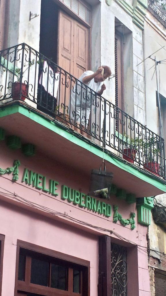 A basket is being dropped from a balcony in Havana to purchase goods