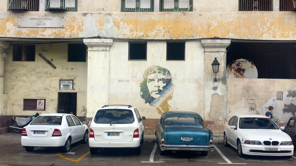 A mix of modern and classic cars in Cuba amongst Che street art