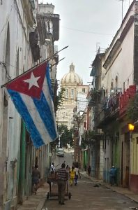 Havana street with Cuban flag and capital building