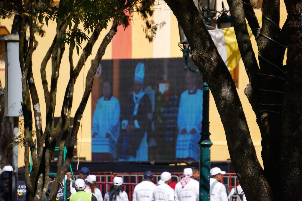 Pope Francis is broadcasted on large TVs in the town square in front of the Cathedral in Signs and banners of Pope Francis show Popemania overtaking the town of San Cristobal de las Casas, Chiapas, Mexico