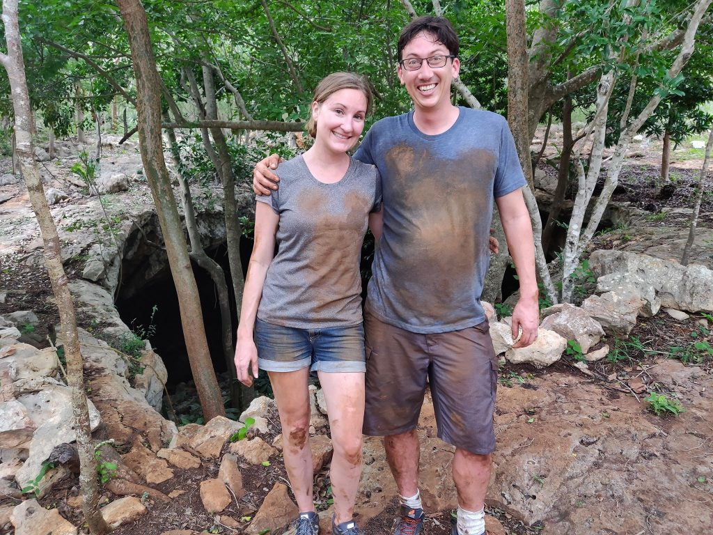 Couple stands muddy after emerging from the Calcehtok cave (grutas de Calcehtok)