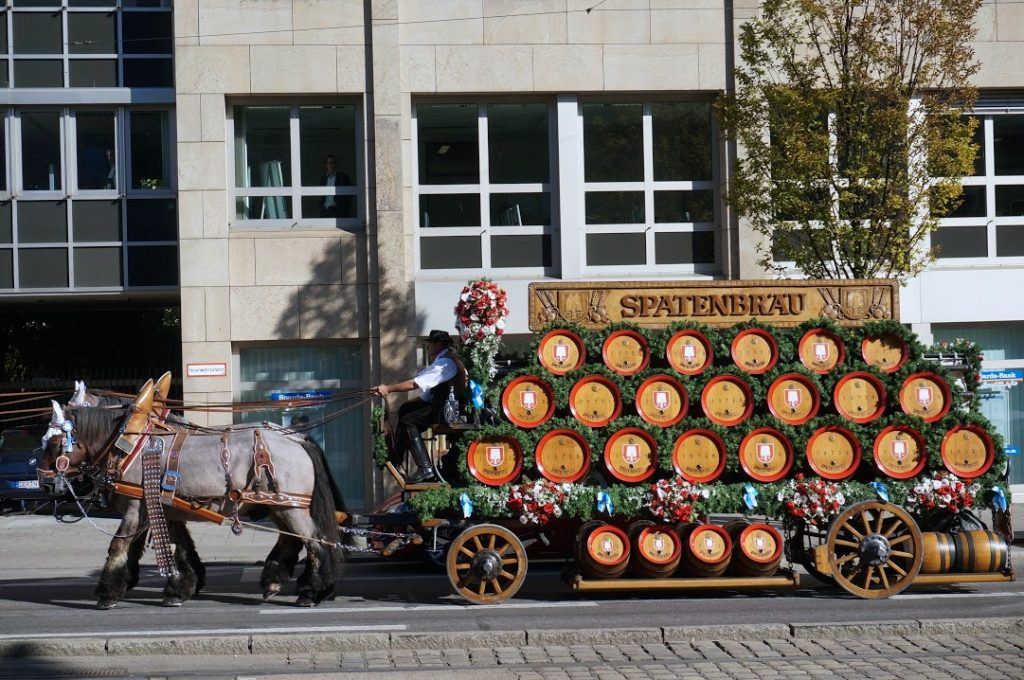 Spaten horses with wagon deliver wooden beer kegs to Oktoberfest