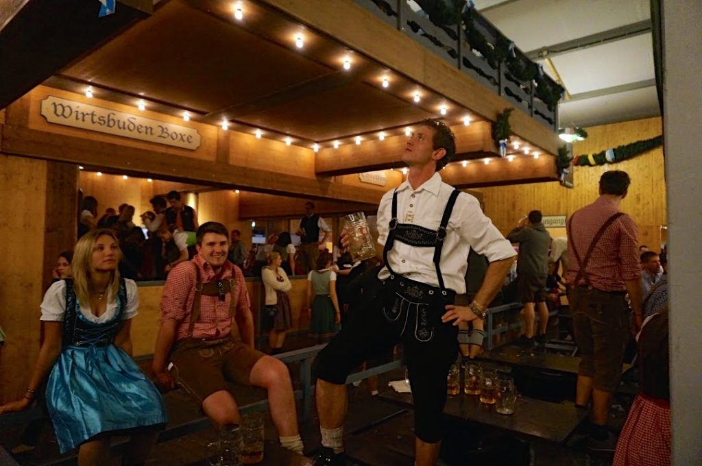 People at Oktoberfest wearing traditional dirndl and lederhosen outfits