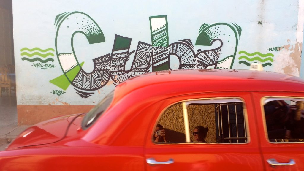 "Cuba travel tips - classic car passing graffiti sign that reads ""Cuba"""