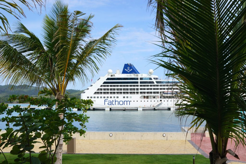 Fathom Adonia between to palms in port at the Amber Cove in Puerto Plata Dominican Republic