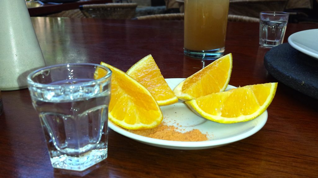 A shot of mezcal in Oaxaca is served with sour orange wedges and sal de gusano (worm salt)
