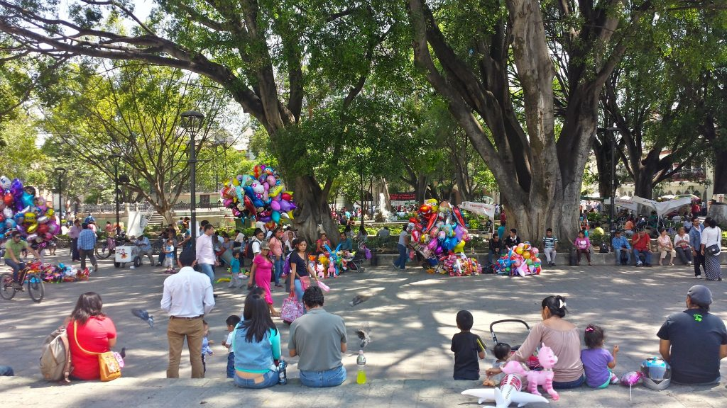 People enjoying local life and balloons in the Oaxaca Zocalo which is the central square in Oaxaca Mexico