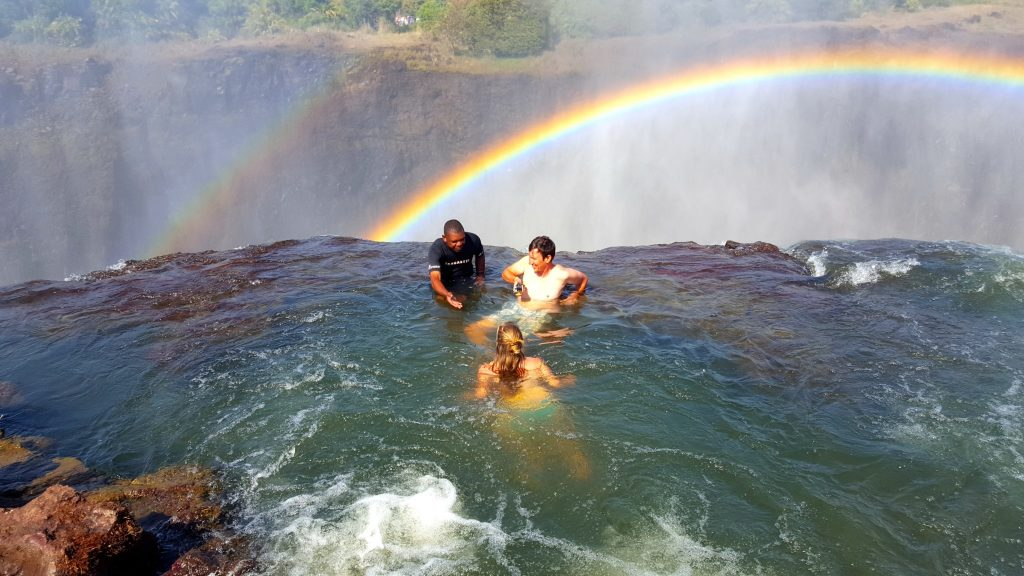 Swimming in Devil's Pool Victoria Falls Zambia with rainbow