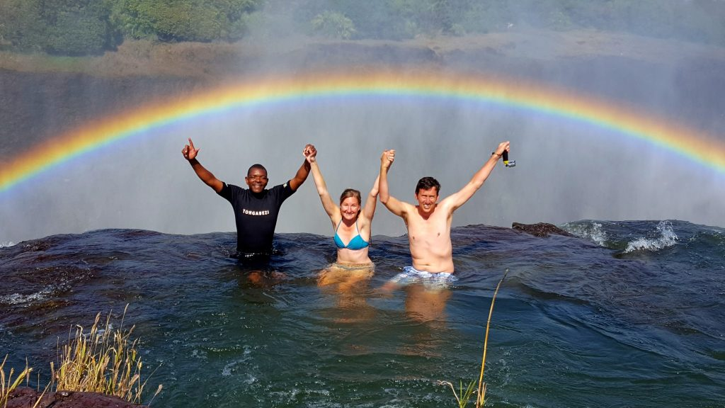 Couple sitting in Devil's Pool Victoria Falls with rainbow contemplating is Devil's Pool worth it