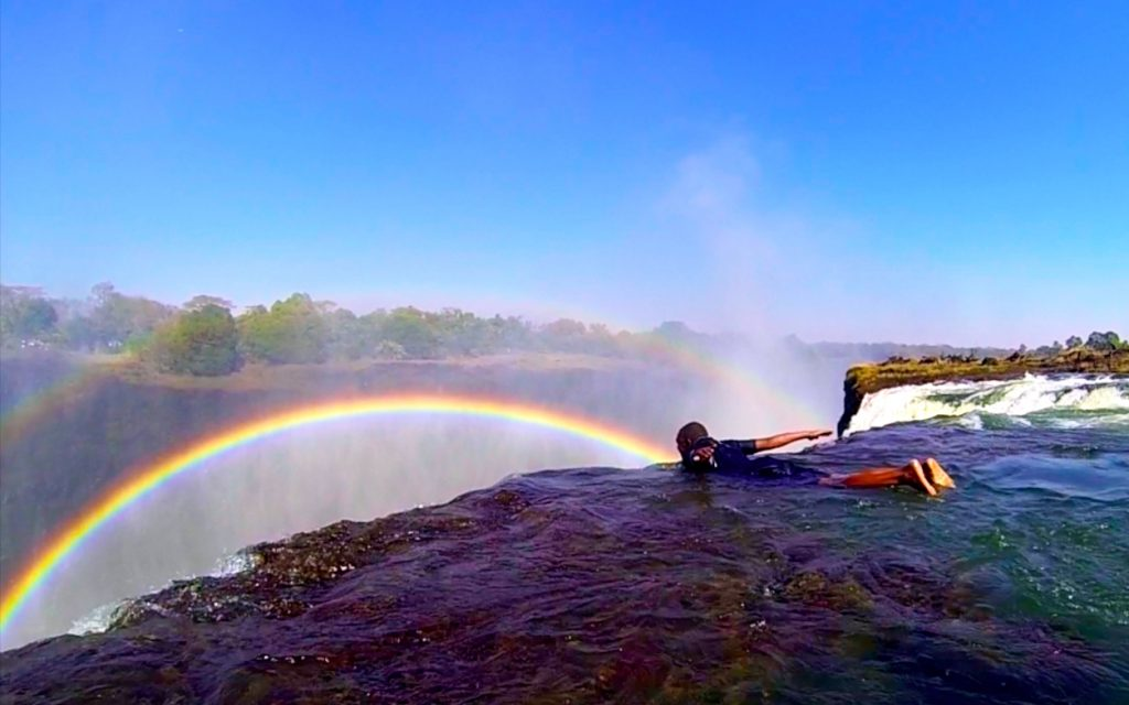 Guide hangs over the edge of Devil's Pool Victoria Falls but there has been no Devil's Pools deaths at Victoria Falls, maintaining a good safety record