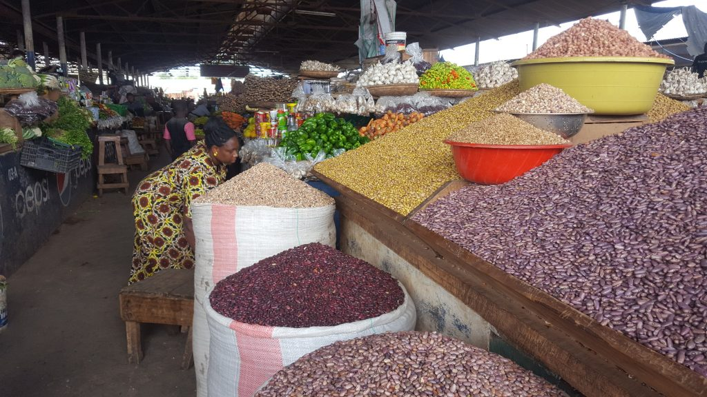 local market in Tanzania Africa - woman selling beans and rice