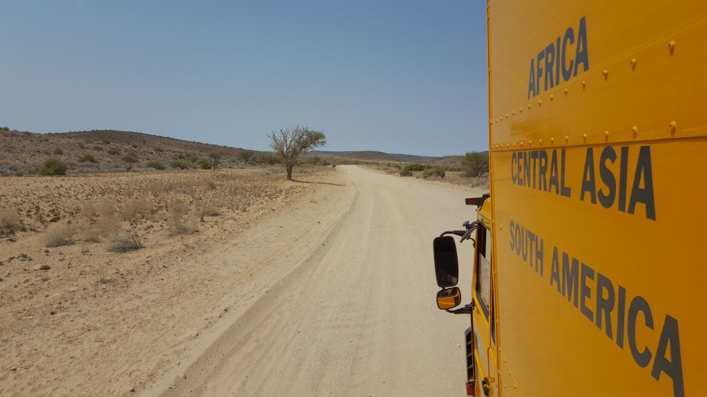 Oasis Overland truck driving on dirt road in Namibia during the Nairobi to Cape Town Itinerary