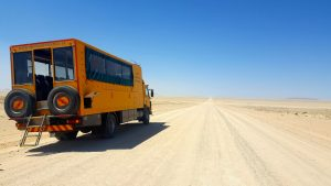 Oasis Overland truck on a dirt road traveling from Nairobi to Cape Town