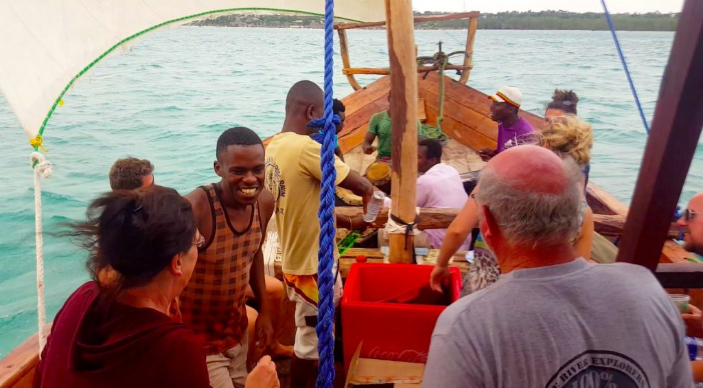 People dancing to drummers on wooden boat during Zanzibar Booze Cruise (Sunset cruise)