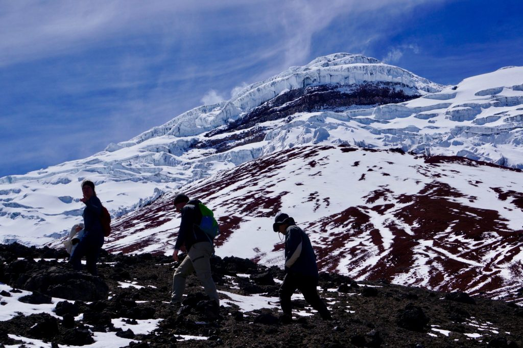 Three people hike of the Cotopaxi Volcano in Ecuador