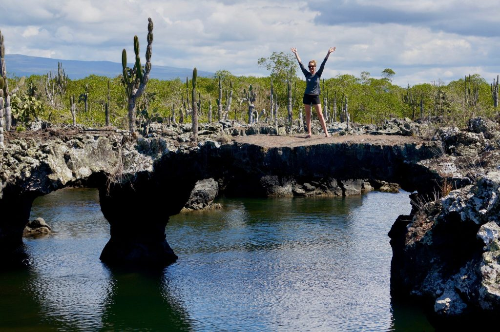 """Heather standing atop the tunnels during """"los tuneles"""" day tour in the Galapagos"""