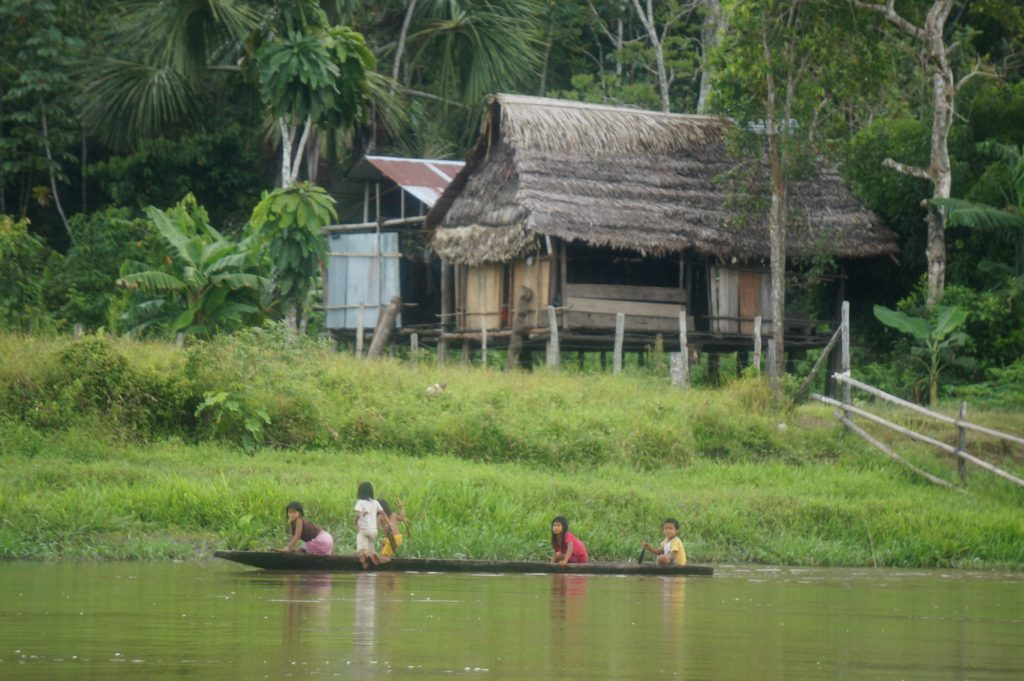 Boat in front of huts on the Napo River in the Ecuadorian Amazon