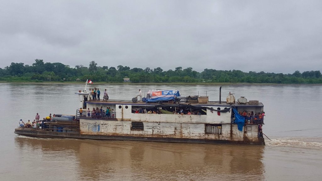 A rickety slow boat on the Napo River with passengers and people on hammocks