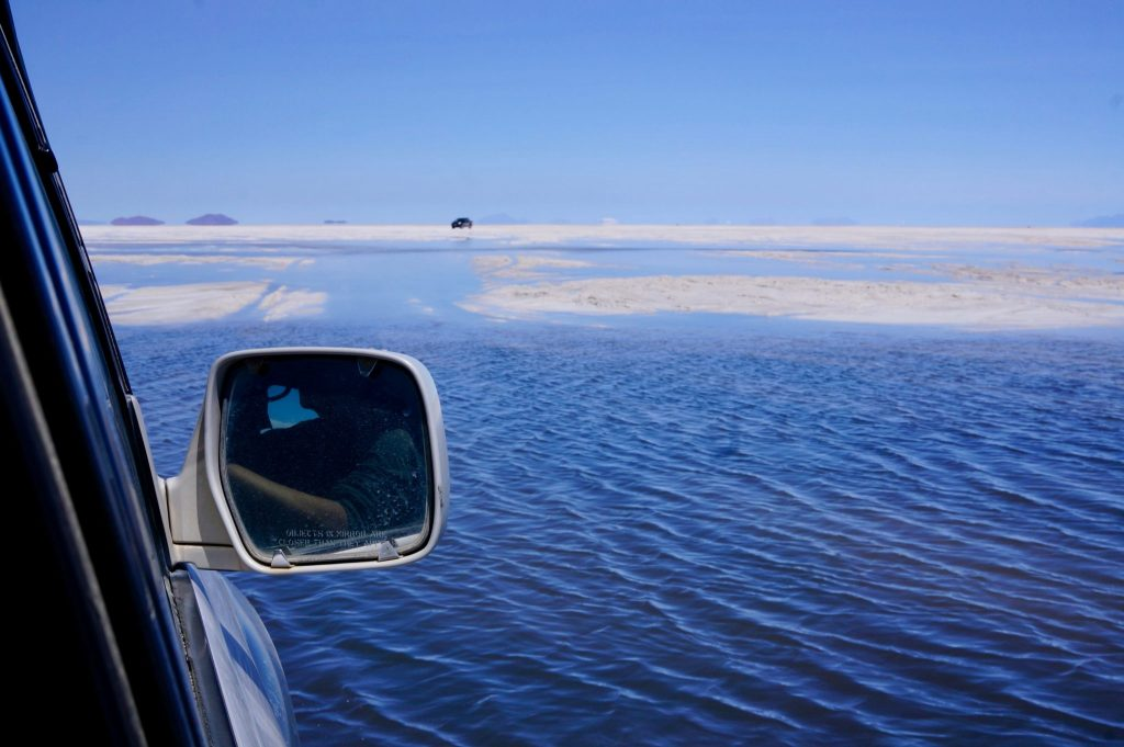 Driving over flooded Bolivia salt flats in the salar de uyuni during a tour