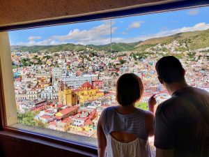 Couple looking at colorful Guanajuato from above the town
