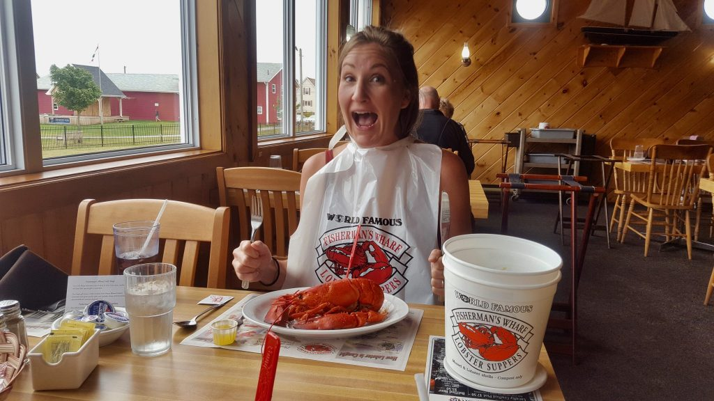 Woman eating lobster supper at Fisherman's Wharf PEI