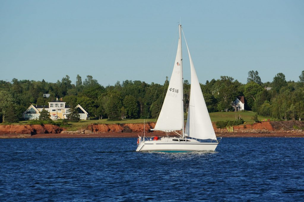 Sailboat and red cliffs in PEI's Charlottetown Harbour
