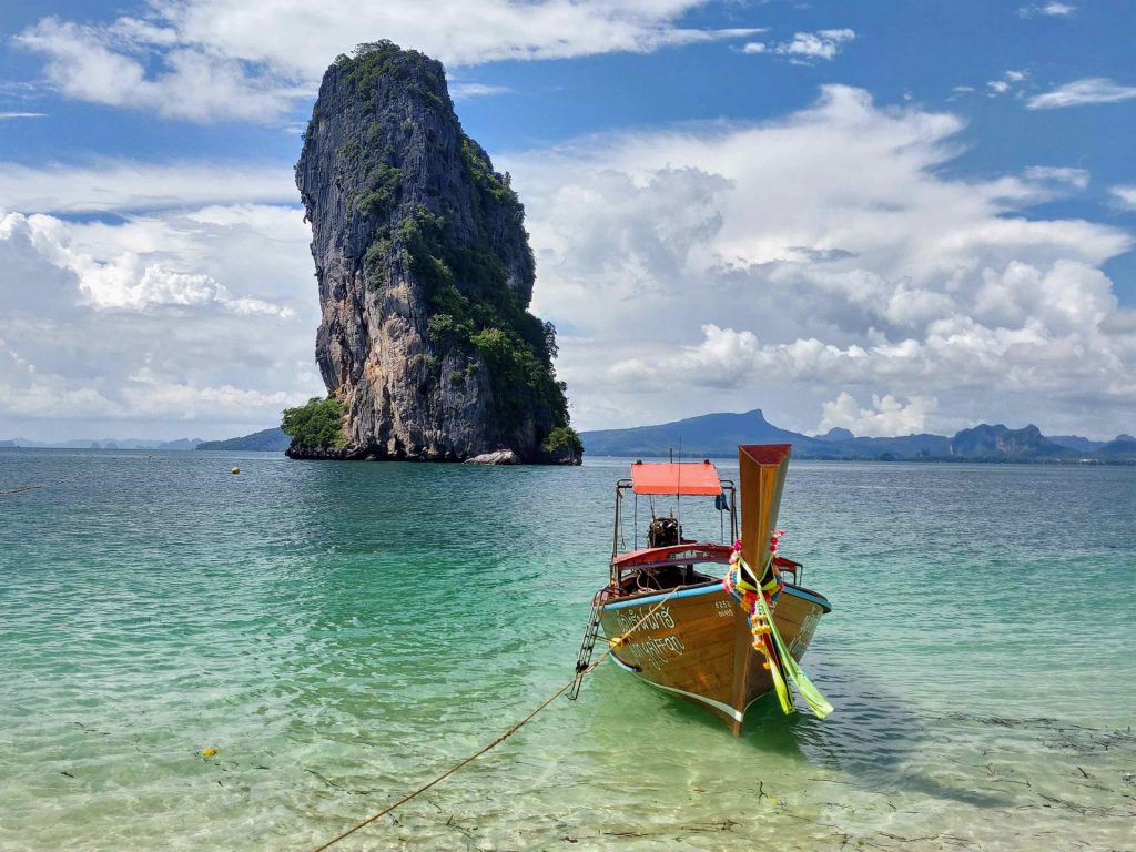 Long tail boat in front of tall limestone island in the sea