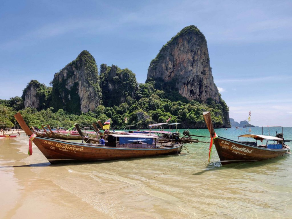 Longtail boats in the ocean in front of limestone cliffs
