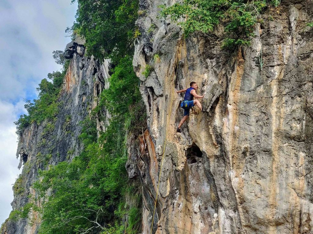 Man rock climbing on cliff in Railay Thailand