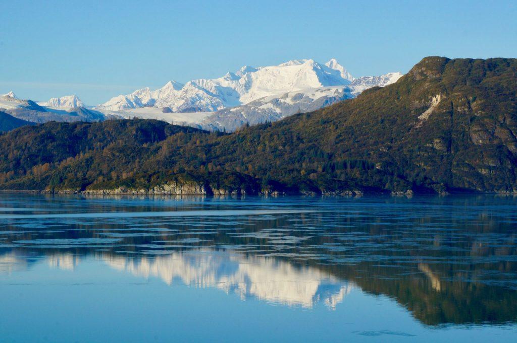 Entering Glacier Bay National Park Alaska, mountain range reflecting in icy bay waters