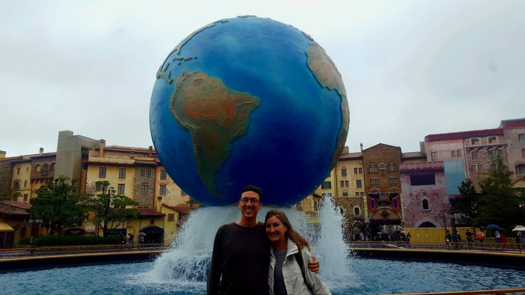 John and Heather, of Roaming Around the World, standing in front of a globe
