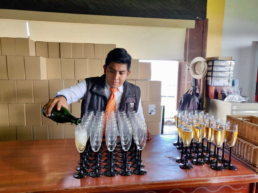 Mexican man pouring sparkling wine at Finca Sala Vive by Freixenet during wine tour from Queretaro