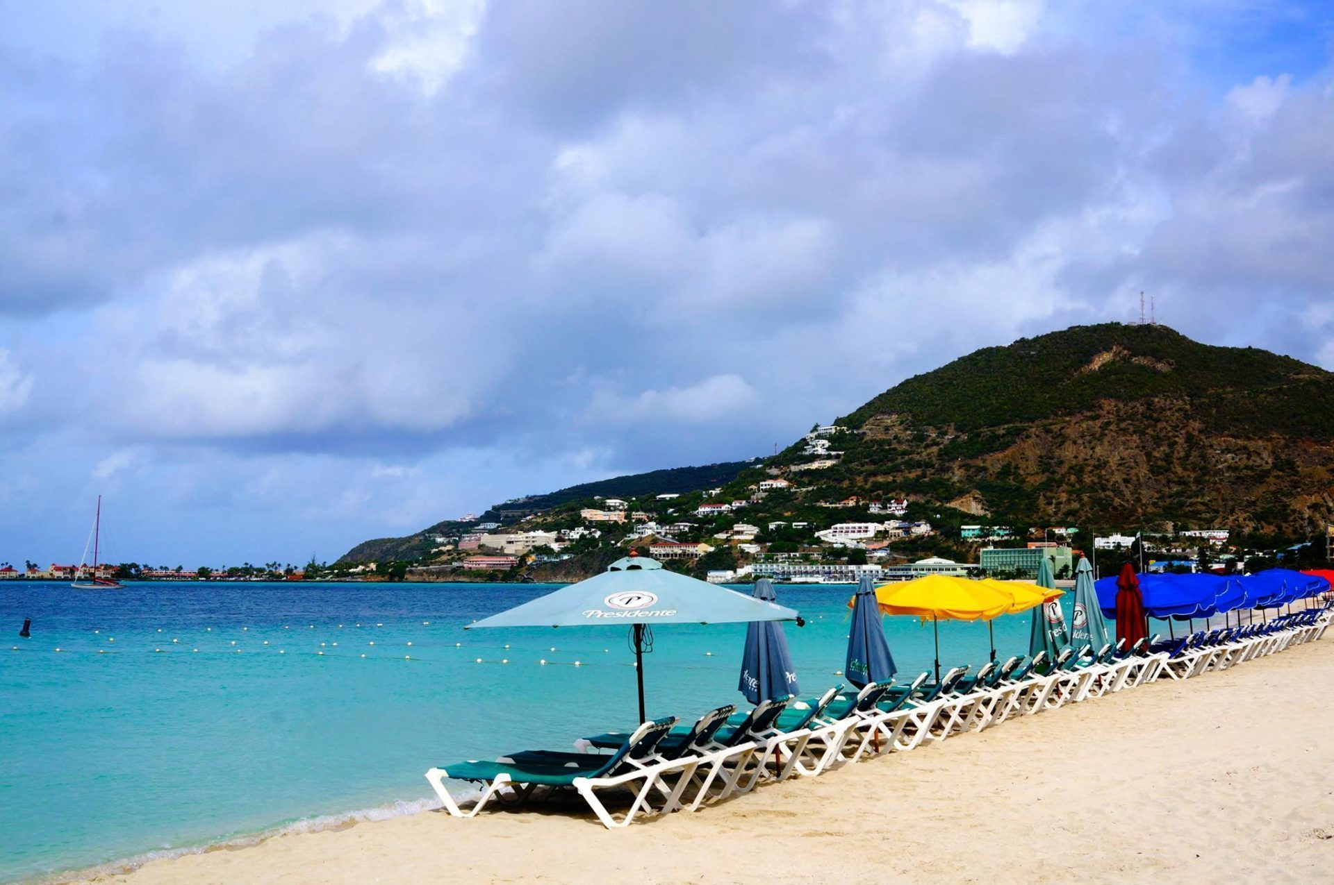 St Maarten beach with umbrellas and beach chairs and blue ocean water