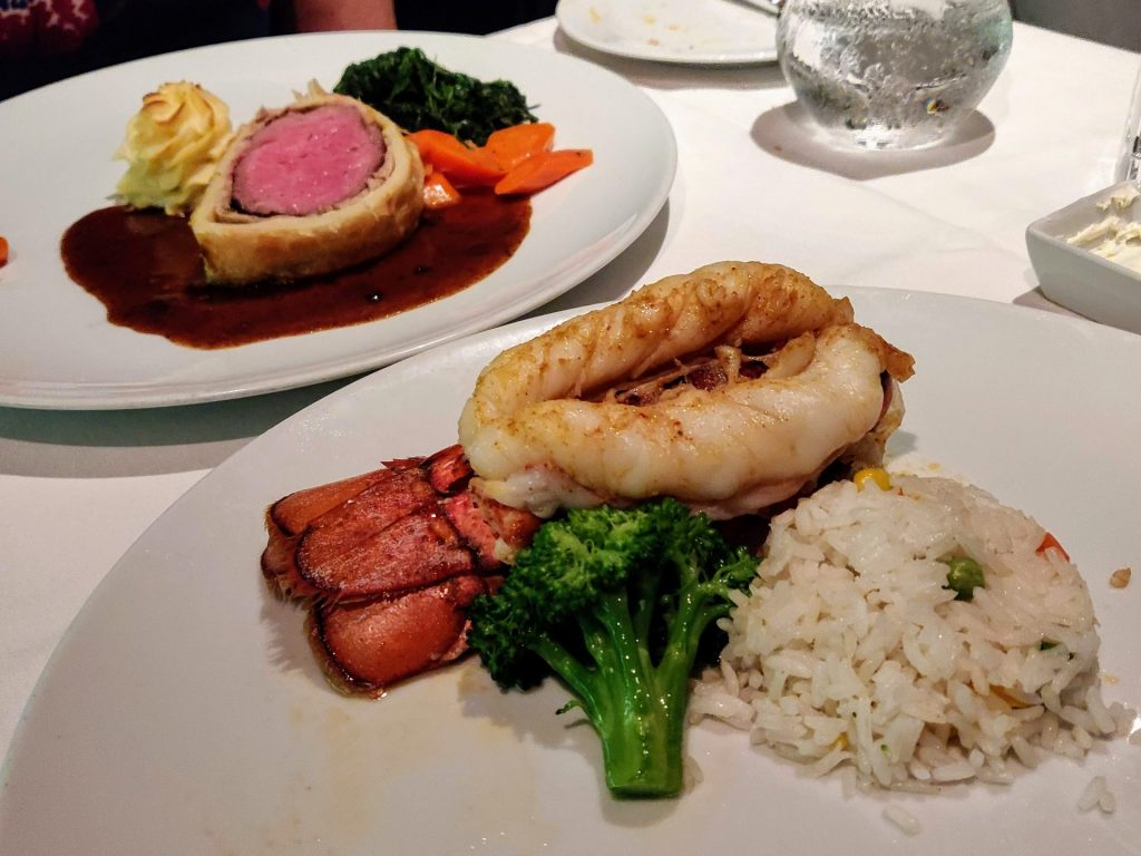 two main courses at a cruise dinner: lobster on one plate, beef wellington on another