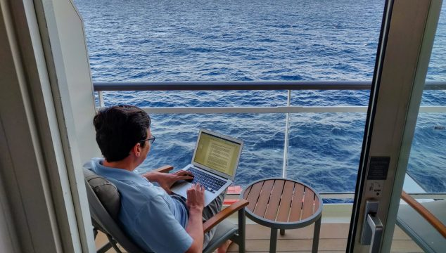Man using wifi on laptop from a cruise ship balcony