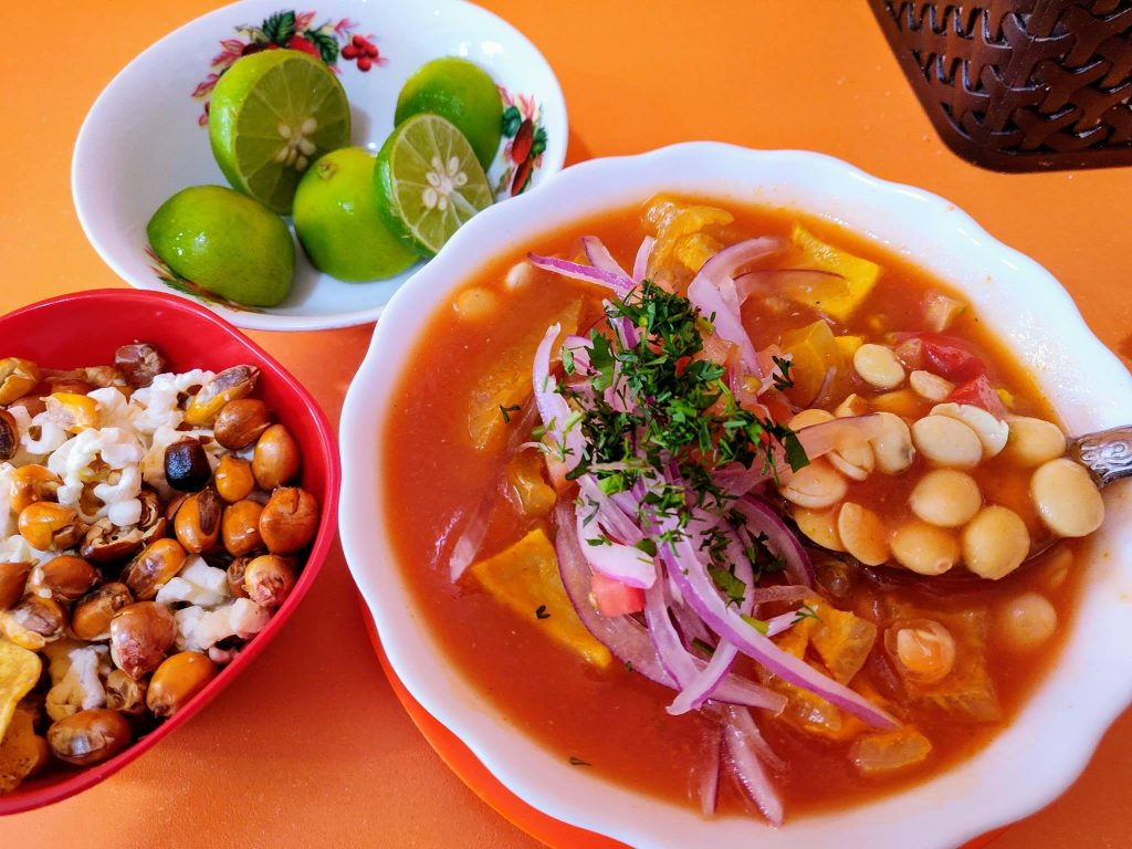 Ceviche de Chocho in a bowl alongside a dish of limes and bowl of popcorn